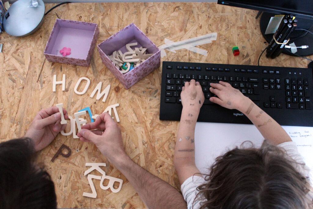 Vater und Tochter sitzen nebeinander am Pult und arbeiten. Die Tochter schreibt auf der Tastatur und der Vater legt mit Holzbuchstaben Wörter.