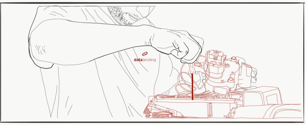 Das Bild zeigt einen Mann mit einem databinding-Tshirt, der etwas mit einem Schraubenzieher repariert.